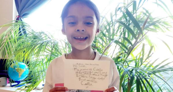 Pupil holding letter written to ESMS community member